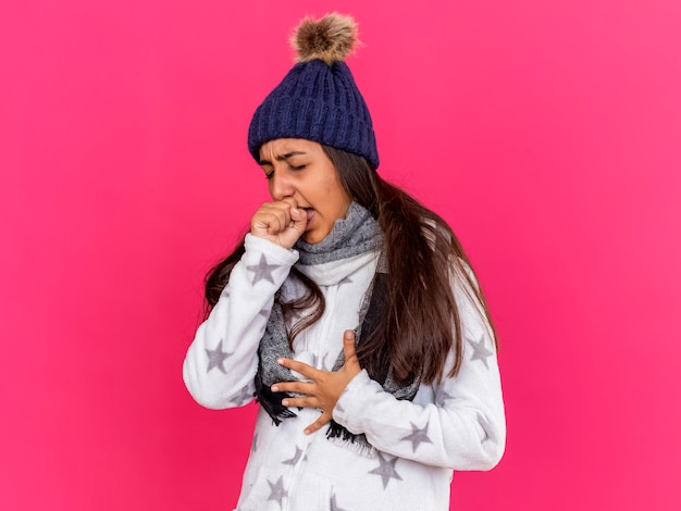 스카프와 함께 겨울 모자를 쓰고 기침 어린 아픈 소녀 핑크에 고립 된 손으로 입을 덮여