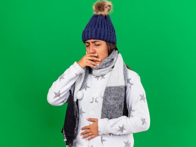 녹색 배경에 고립 된 위장에 손을 넣어 스카프와 겨울 모자를 쓰고 기침 어린 아픈 소녀