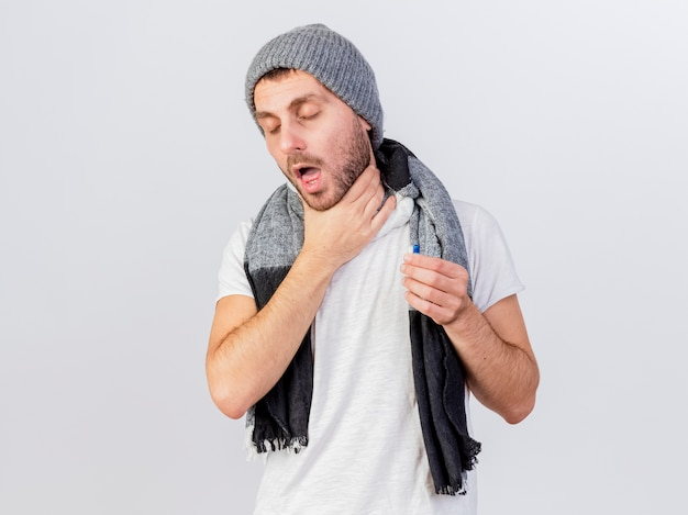 Tosse giovane uomo malato che indossa cappello invernale e sciarpa afferrò la gola e tenendo la pillola isolato su bianco