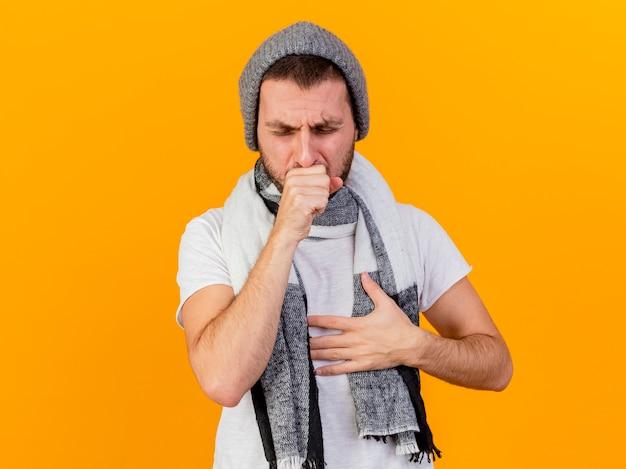 Tosse giovane uomo malato che indossa cappello invernale e sciarpa mettendo la mano sul petto isolato su giallo