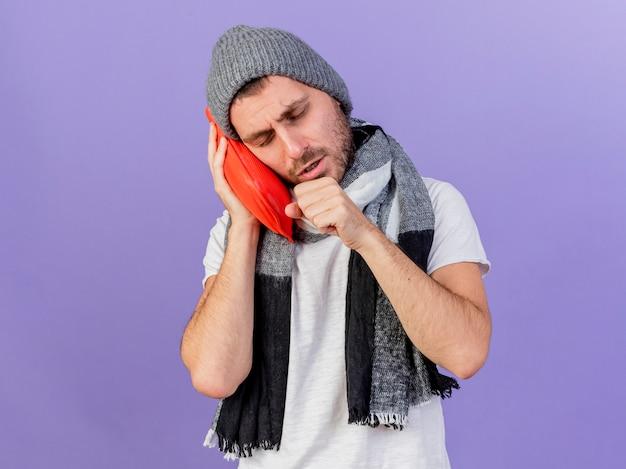 Tosse giovane uomo malato che indossa un cappello invernale con sciarpa tenendo la bottiglia di acqua calda sulla guancia isolato su viola