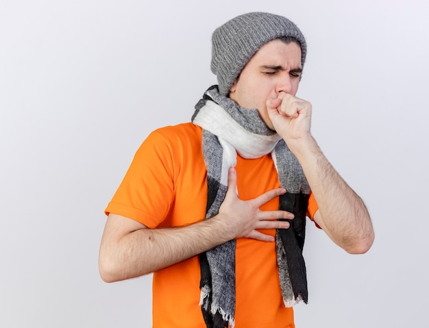 Coughing young ill man wearing winter hat with scarf putting hand on mouth isolated on white