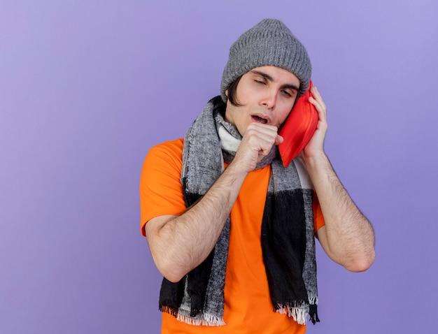 Tosse giovane uomo malato che indossa un cappello invernale con sciarpa che mette il sacchetto di acqua calda sulla guancia isolato su sfondo viola