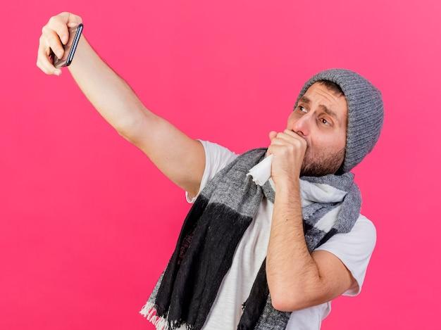스카프와 겨울 모자를 쓰고 기침 젊은 아픈 남자는 셀카를 가지고 분홍색 배경에 고립 된 입에 손을 넣어