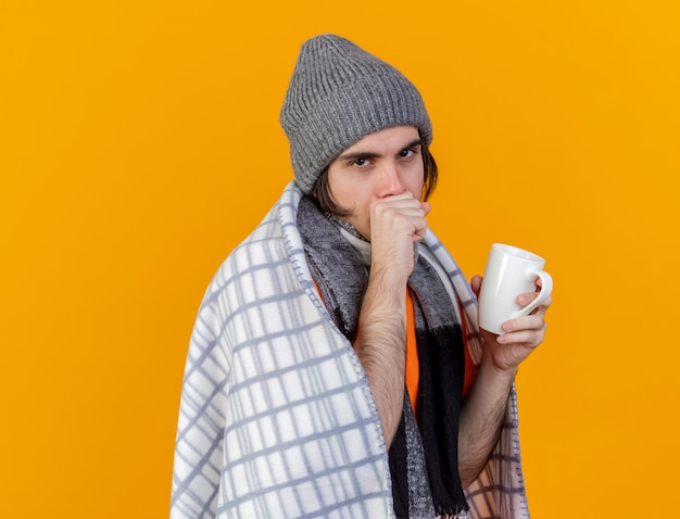 Coughing young ill man wearing winter hat with scarf wrapped in plaid holding cup of tea isolated on orange