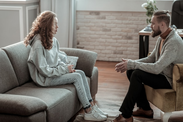 방과 후 카운슬러. 방과 후 카운슬러를 방문하는 청바지와 회색 까마귀를 입고 아름다운 세련된 소녀