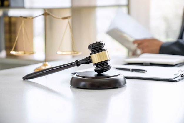 Counselor in suit or lawyer working on documents. judge gavel and scales of justice.