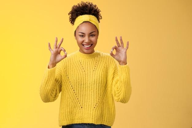 完了したと数えます。セーターのヘッドバンドで自信を持って自信を持ってアフリカ系アメリカ人の女性を見せて大丈夫ok心配しないジェスチャー笑顔自信のある計画はうまくいき、良い結果を喜ばせ、黄色の背景を応援します。