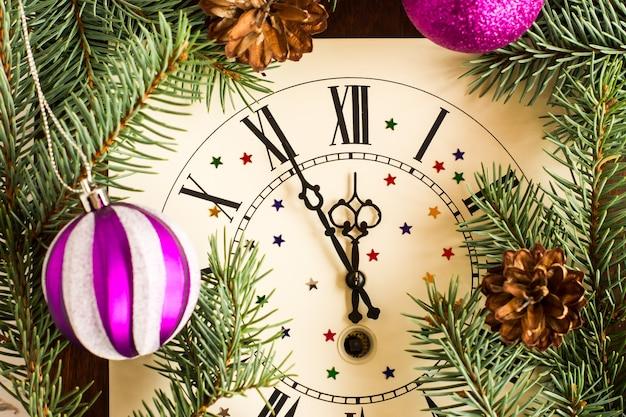 Обратный отсчет до полуночи. ретро-часы с еловыми ветками, шишками и елочными шарами. счастливой новой концепции года.