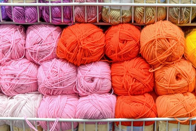 Прилавок в магазине для вязания и рукоделия мотками цветной шерстяной пряжи. нитки разных ярких цветов на рядах в магазине. розничная торговля товарами для хобби, рукоделия и вязания. выборочный фокус