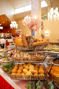 A counter with bread products on a buffet table in a restaurant