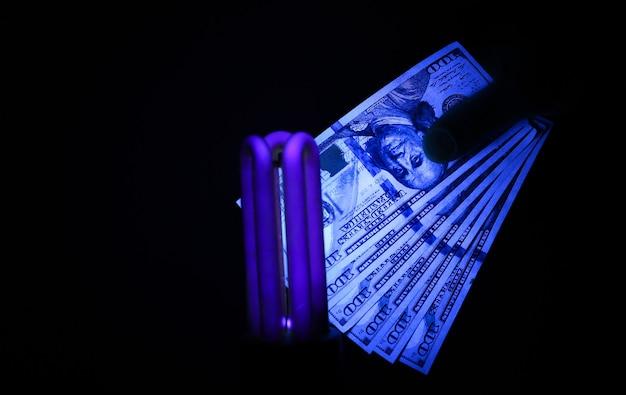 紫外線ランプによる偽金チェック。詐欺犯罪。