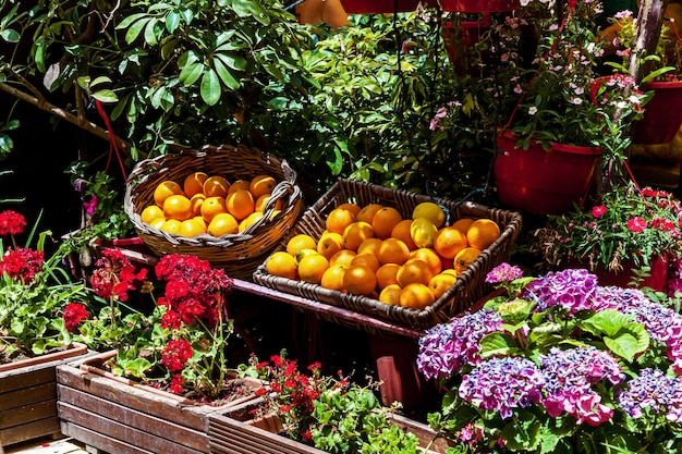 市場にある鮮やかな花とオーガニックフルーツのカウンター。