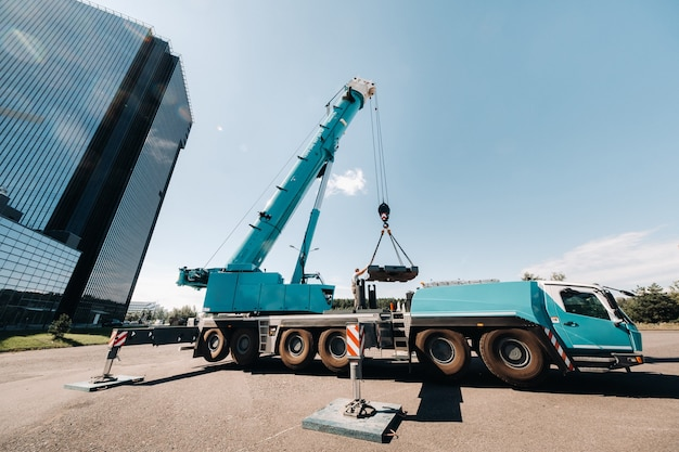 The counterweight is installed by an unrecognizable worker on a large blue car crane and is prepared to work on a site next to a large modern building.