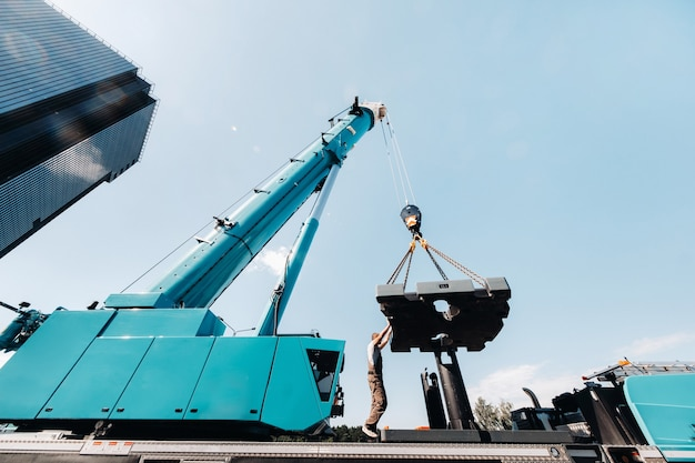 The counterweight is installed by an unrecognizable worker on a large blue car crane and is prepared to work on a site