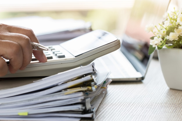Counting on calculator for checking financials analyzing documents paperwork