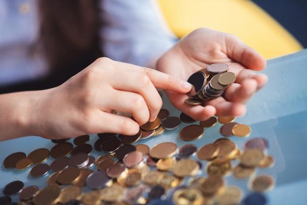 コインを数える。コインを数える女の子の手の写真を閉じる