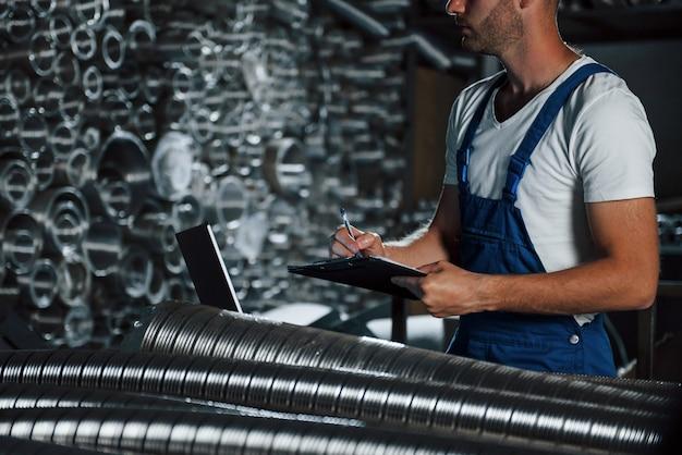 Подсчет предметов. мужчина в военной форме работает на производстве. современные промышленные технологии.
