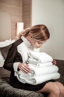 수건 계산. 고객에게 건네주기 전에 흰 수건을 세는 금발 머리 가정부
