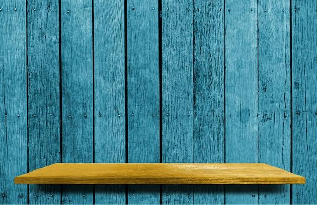 青い木製の背景を持つ黄色の空の棚countre
