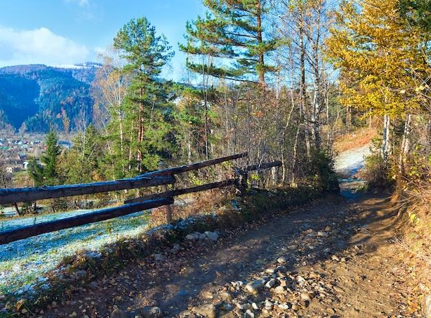 Загородная грязная дорога и первый осенний иней на окраине горной деревни