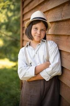 Деревенская девушка позирует, прислонившись к деревянной стене здания.