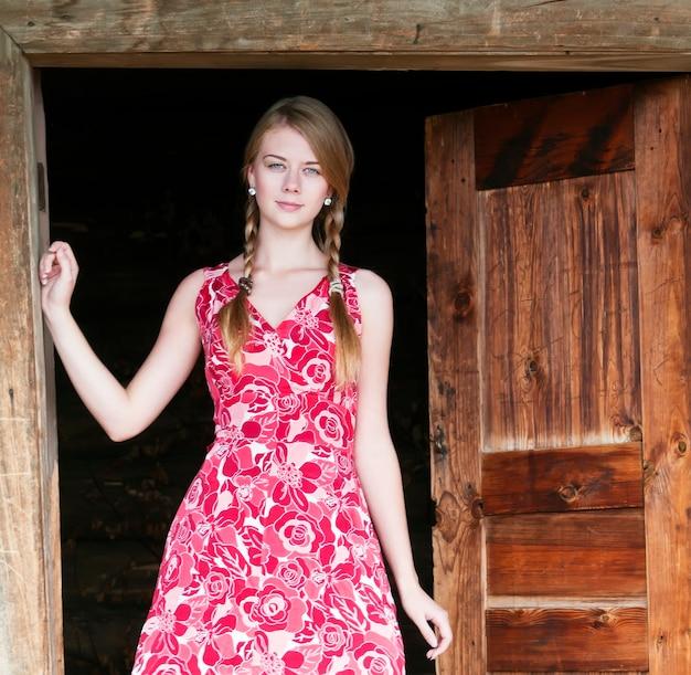 오래 된 집의 출입구에 서있는 시골 소녀