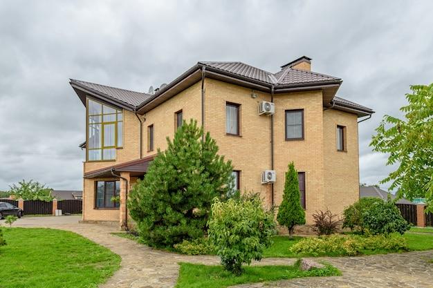 Деревенский дом. зеленый газон и деревья вокруг дома.