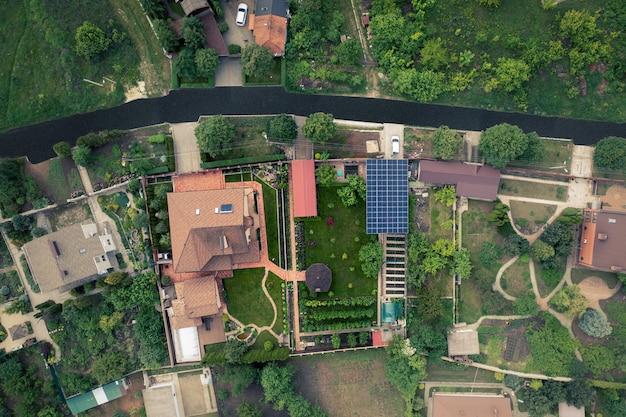 Загородный дом в красивом дворе с солнечной электростанцией из солнечных батарей.