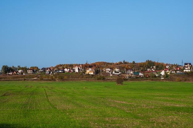 田舎暮らし。丘の上の村。澄んだ青い空を背景にした丘の上にあるモダンな村の前にある緑の春の野原。農地。