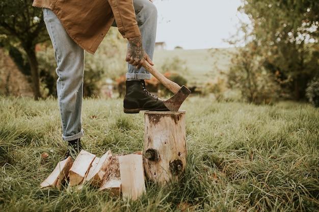 フィールドで斧で木を分割する田舎の男