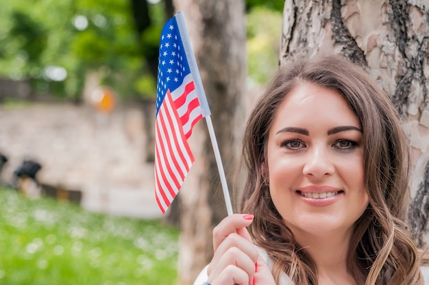 Страна, патриотизм, день независимости и концепция людей - счастливая улыбающаяся молодая женщина в белом платье с национальным американским флагом