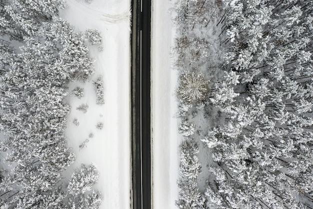 美しい雪に覆われた風景、空撮、ドローン写真を通る田舎道