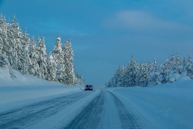 Проселочная дорога в заснеженном лесу. зимний вечер. одинокая машина
