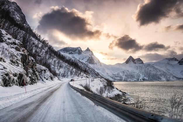 日没時の冬の海岸線の雪の谷の田舎道