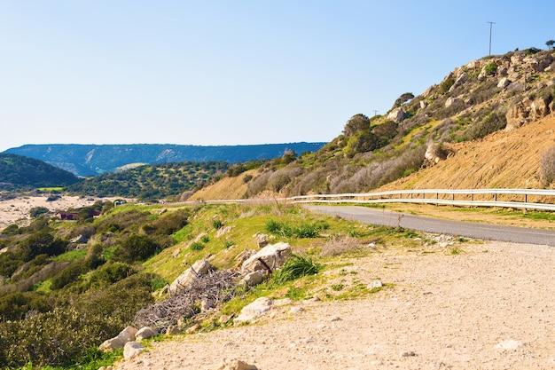 田舎道の曲がりくねった道。緑の草で丘を登る道