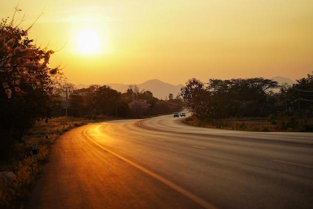 태국에서 움직이는 자동차와 아름다운 황금빛 일몰을 배경으로 하는 시골길.