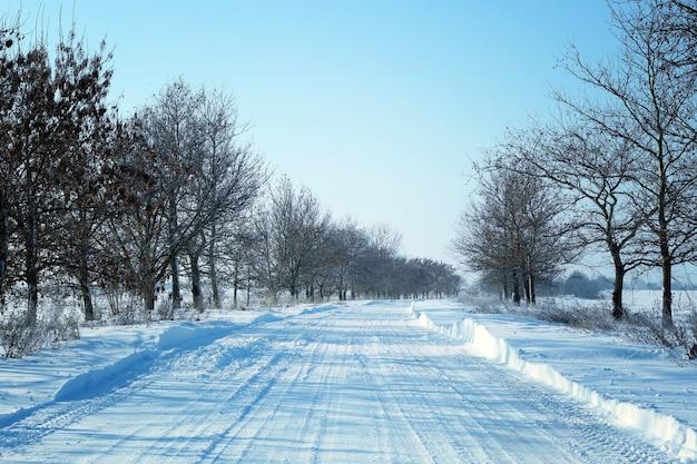 晴れた日は雪に覆われた田舎の空の道