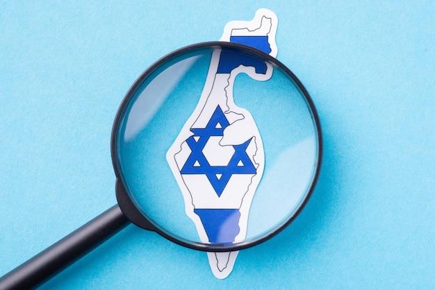 Страноведение израиля. увеличительное стекло на карте израиля на синем фоне