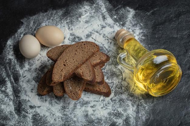 컨트리 스타일. 밀가루 배경에 계란과 기름으로 갈색 빵을 슬라이스.