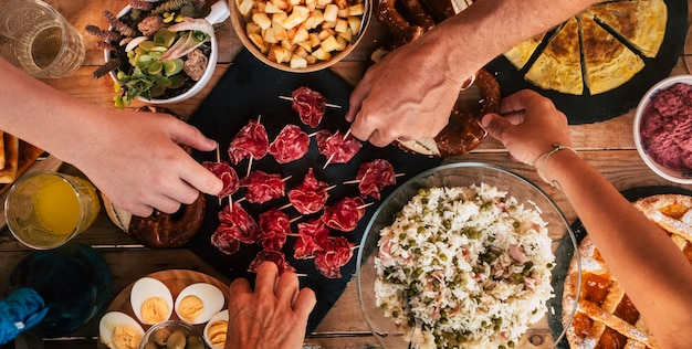 Country style wooden table full of fresh food and people hands