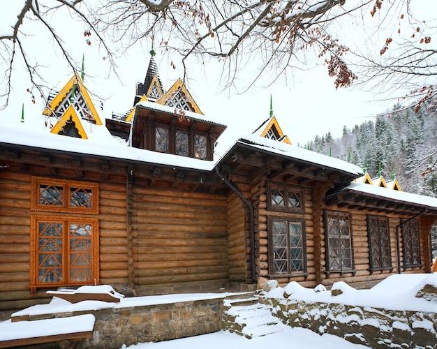 Загородный деревянный дом и зимний лес за ним (карпаты, украина)