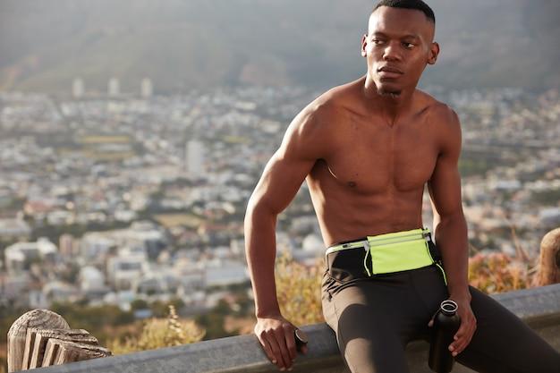 田舎の健康的なアクティブなライフスタイルのコンセプト。筋肉質の体を持った集中民族男性、水で満たされたスポーツボトルを保持し、全力疾走後に休憩し、マラソンを実行する準備ができて、外でジョギングします