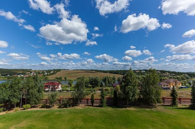 牧草地、森、空を背景にした田園風景。田舎の風景。
