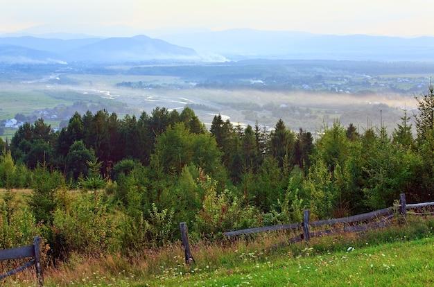 後ろに木製の柵と山のある田園風景