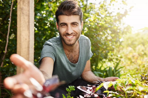 Countryside life, naature. close up outdoor portrait of young attractive bearded caucasian man in blue t-shirt smiling