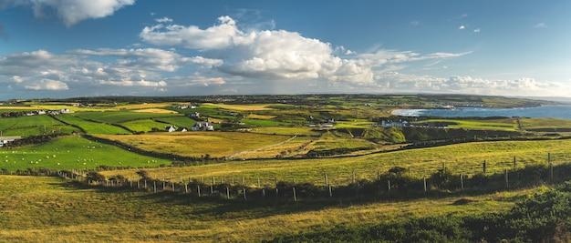 Панорамный вид сельской местности на зеленые поля под голубым облачным небом пейзаж северной ирландии