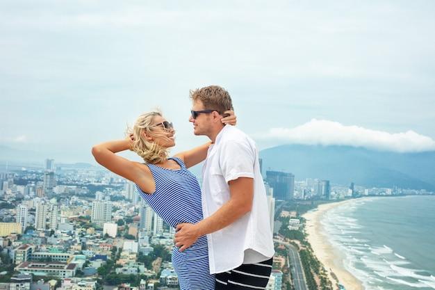 Пара мужчина и женщина счастливы, красивые вместе на фоне моря и города в летний день