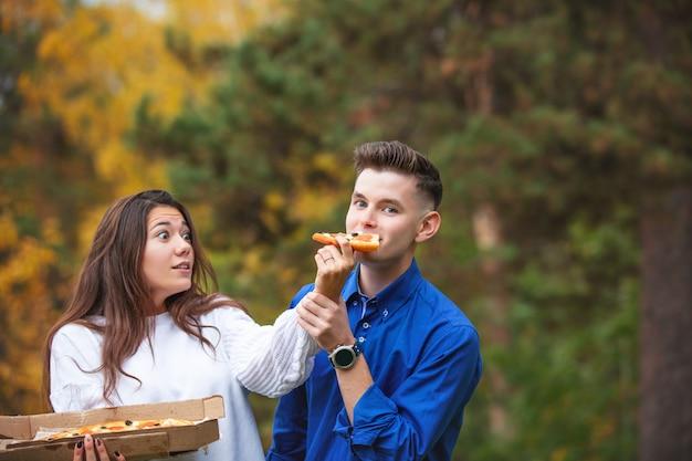 Пара мужчина и женщина, молодая, забавная, красивая, вместе наслаждаются пиццей и общаются на пикнике на природе