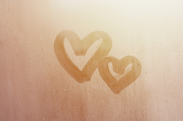 Couple of abstract blurred love heart symbol drawn by hand on the wet window glass with sunlight background.